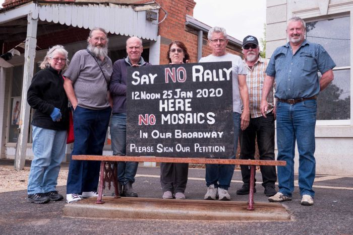 Seven people stand behind a bench with a hand-painted sign that says: say no rally - no mosaics in our broadway'