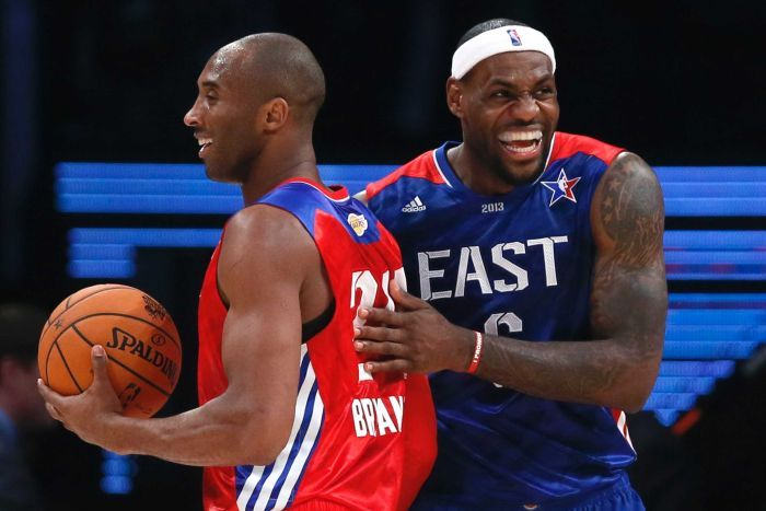 LeBron James laughs as he pats Kobe Bryant, holding a basketball, on the back during the NBA All-Star game.