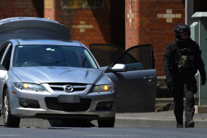 A silver sedan is parked on the road with all doors and the boot open, a person in black bomb squad gear stands next to the car.