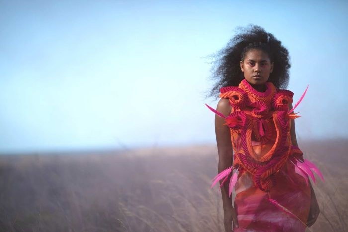 A young indigenous model wears a contemporary looking dress made using traditional indigenous weaving practices