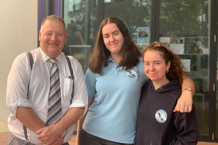 An older male (the school principal) standing next to two female year 11 students. They are all smiling.