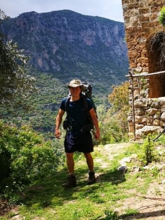 A man in hiking clothing and a hat stands in front of a vast valley in Lebanon.