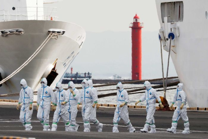 People in white hazmat suits walking across a dock with a ship beside them