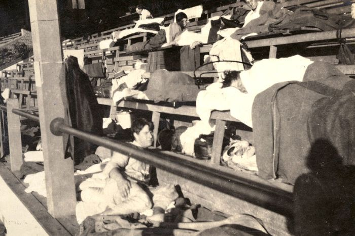 A black and white image of young men sleeping on seats in a grandstand.