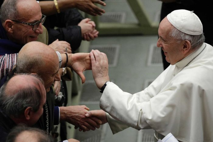 Pope in side profile of Pope in white cap shakes hands with men's outstretched hands.