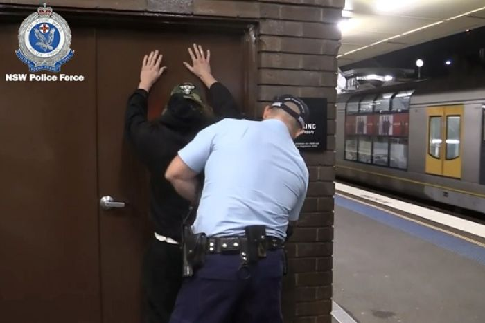 Police frisk search a man at a train station.