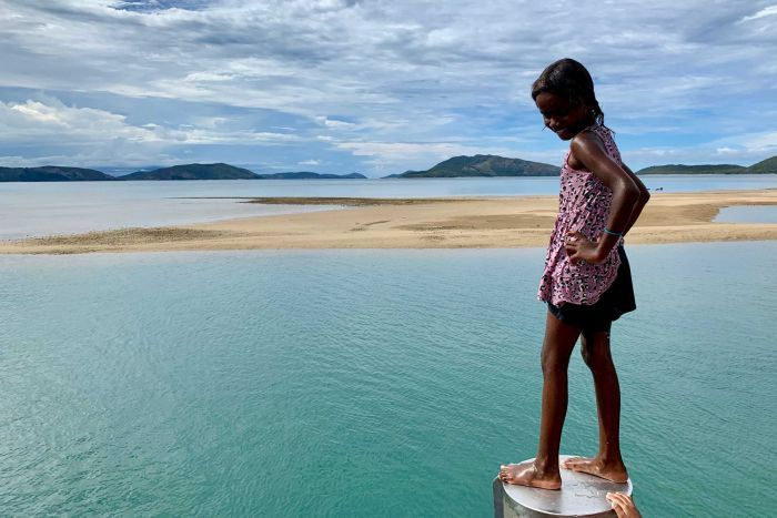 Aboriginal girl stands on podium at jetty smiling with hands on hips looking down