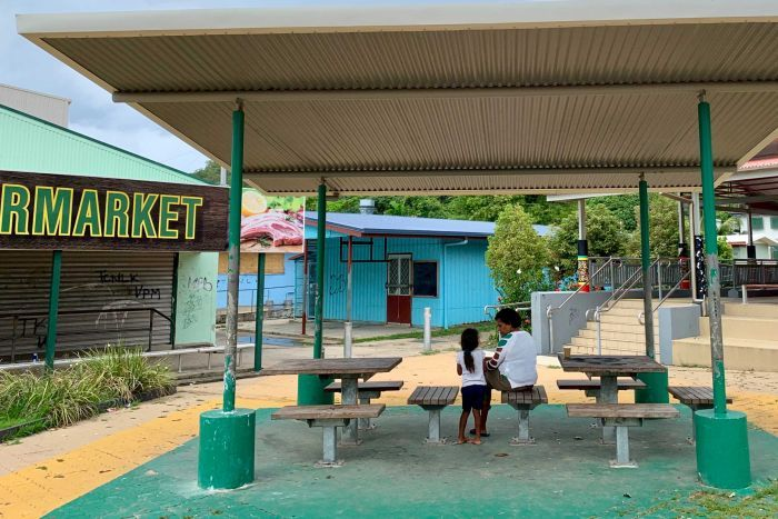 A woman and child sitting on table and chairs out the front of the grocery shop on Palm Island Jan 2020