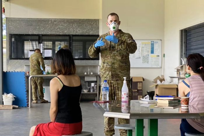 A soldier wearing a face mask and blue gloves stands in front of a table talking to evacuees.