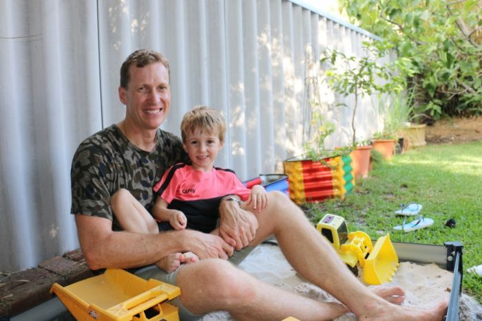 Shane Boladeras and his son Quinn sitting in a backyard sand pit.