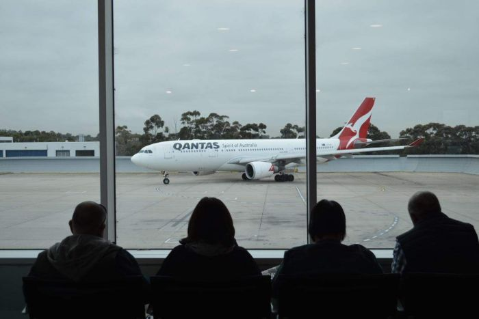 A Qantas plane taxies along a runway in overcast conditions while passengers seated inside watch on.