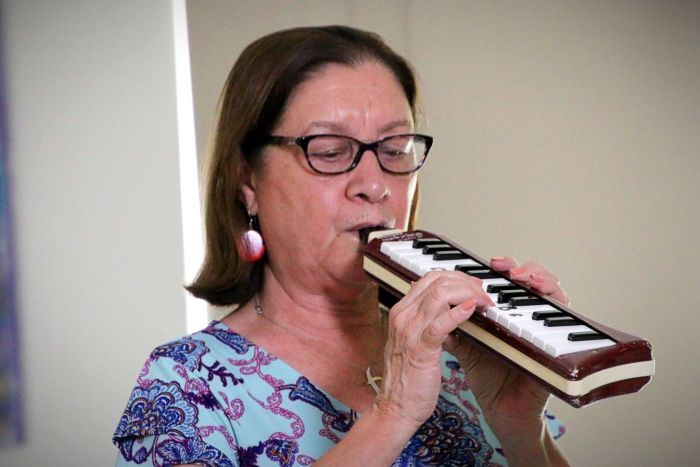 A woman wearing glasses and a floral dress plays a melodica