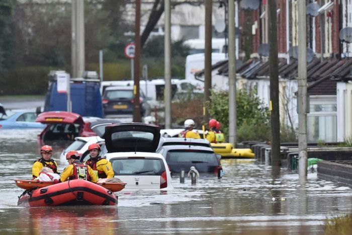 In a flooded street in a town, rescuers dressed in yellow ferry a local resident in a inflatable raft next to houses