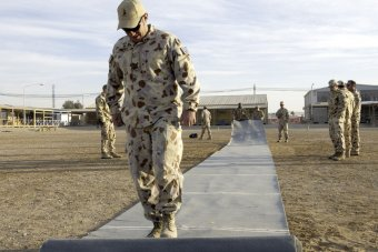 Corporal Paul Sweeney rolls out the pitch before the Boxing Day Test at Kandahar Airfield