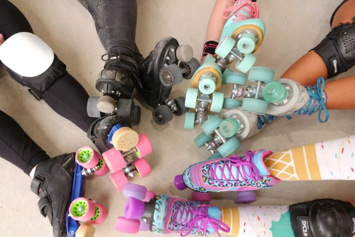 Five pairs of feet wearing skates in a circle on the ground.