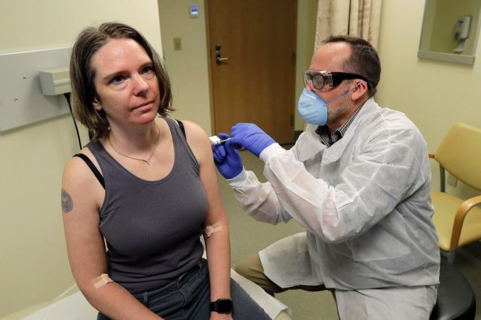 Jennifer Haller receives an injection from a man dressed in a suit and wearing a mask.