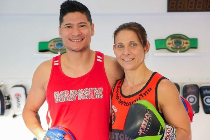 A man and woman stand in a boxing gym side by side smiling at the camera.