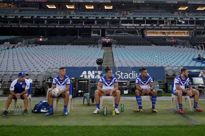 The interchange players of the Bulldogs NRL team sit on a bench in front of an empty grandstand.