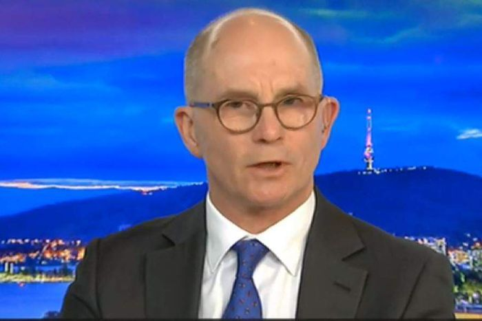 A man with a bald head and glasses in a suit and tie.