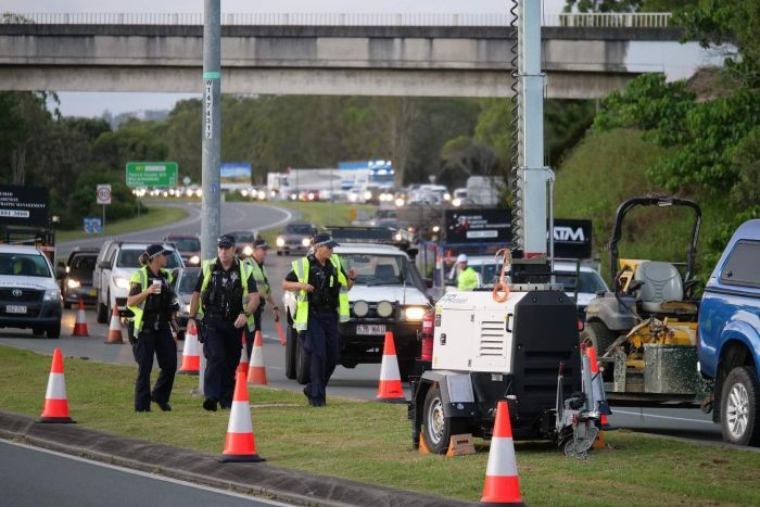 Police at the head of a long line of traffic on a highway