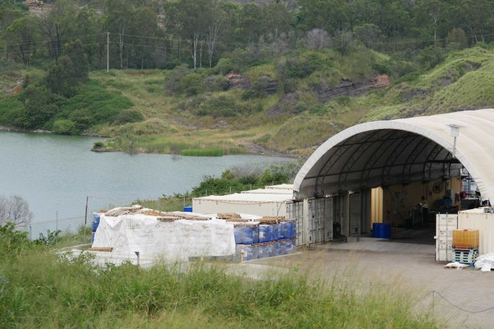 A large hanger style shed with shipping containers in front of a small lake