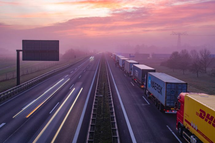 On a bright pink morning, you see a line of trucks on an otherwise empty Autobahn.