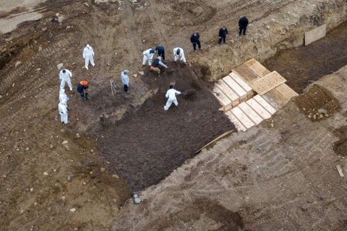 The drone shot in a protective device digging a mass grave