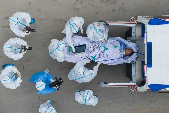 A photo taken from directly above shows a patient being loaded into an ambulance with medics wearing protective suits nearby.