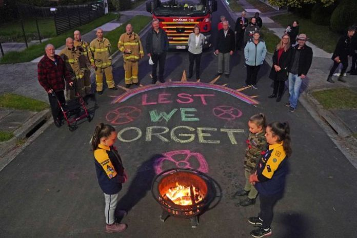 a group of people in the fire department stand on a street afraid that they will forget chalk writing