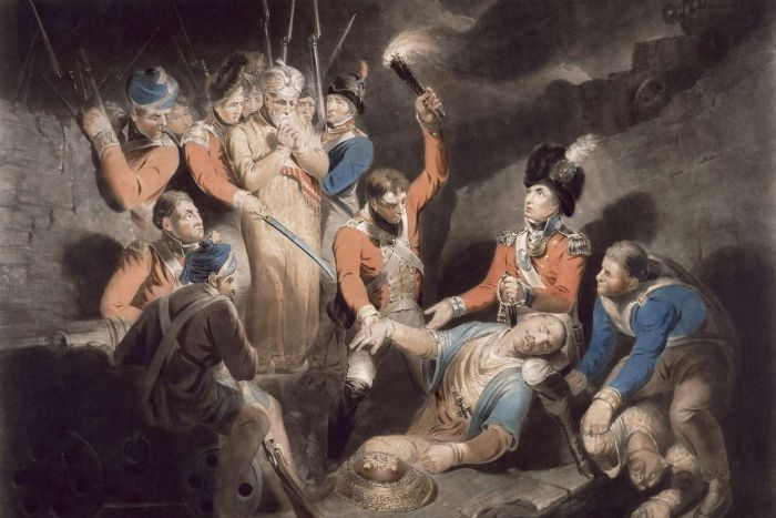 An illustration of British soldiers finding the body of Tipu Sultan, one holds a torch to illuminate the scene.