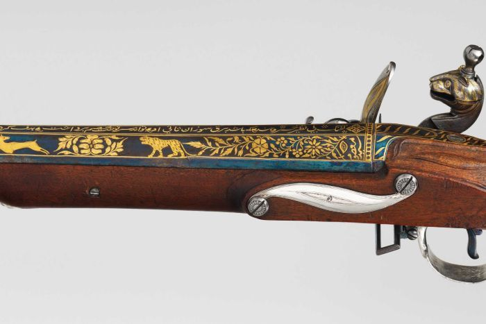 A blunderbuss decorated in gold with tigers, flowers, and tiger stripes. The cock of the rifle is shaped like a tiger's head.