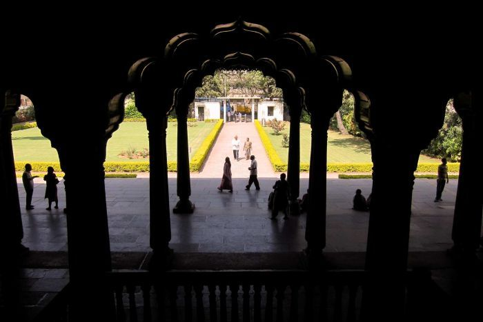 Looking out between dark, dimly lit columns in a palace to a path and entrance. People stand around in the sun.