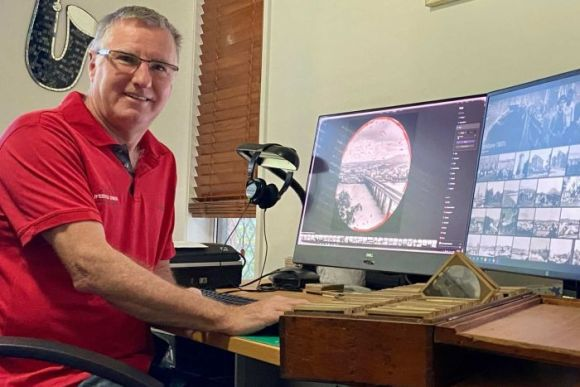 A man sits at his desk. On his computer screens are historic photos that he is restoring.