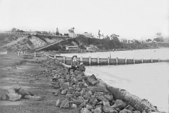 A black and white photograph of a rocky shoreline. A boy sits on the rocks.