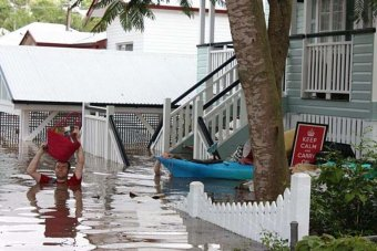 Man carrying a bag above his head wades through floodwaters outside a house