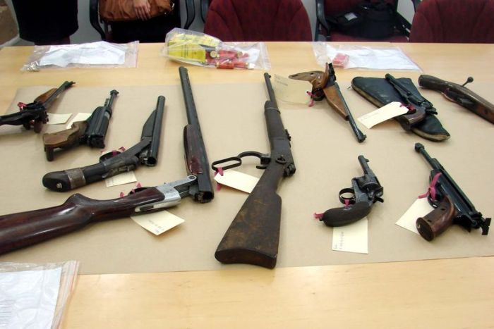 Firearms and ammunition are displayed to the media