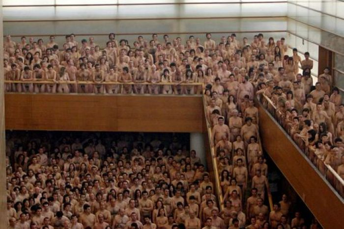 Naked people stand on a mezzanine, staircase and floor.