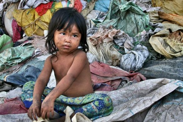 Young girl sits at a Cambodian rubbish dump in Siem Reap