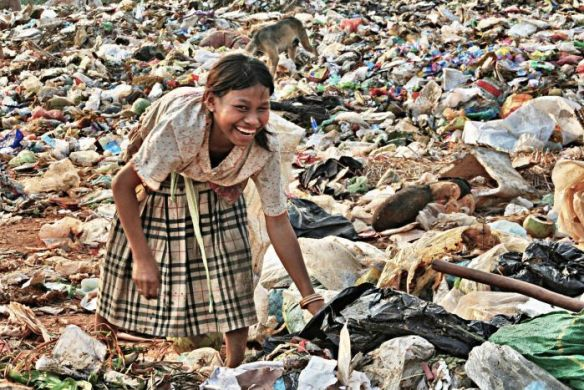 Girl laughs while rummaging for food at a Cambodian rubbish dump