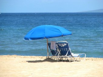Two lounges sit under a beach umbrella at the beach.