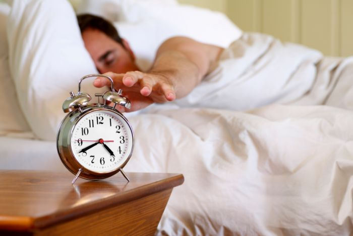 A man reaching out for an alarm clock while still in bed.