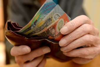 Hands put Australian currency into a wallet