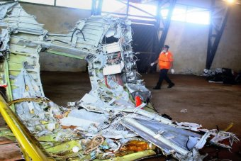 A member of Indonesia's search and rescue team walks past a piece of the plane wreckage.