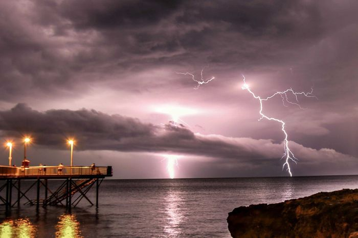 Lightning strikes stand out against a purple, cloudy sky in the distance, with people watching from a jetty on the water.