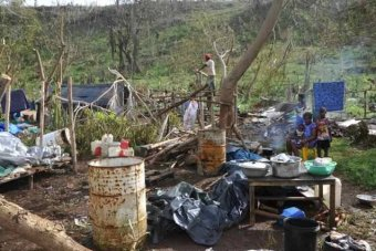 Family sits by fire among ruins of home and garden after Cyclone Pam in Vanuatu
