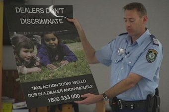 Senior Sergeant Simon Madgwick holds an anti-ice campaign poster.