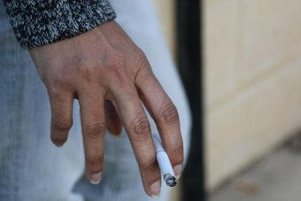 Woman's hand holding a lit cigarette