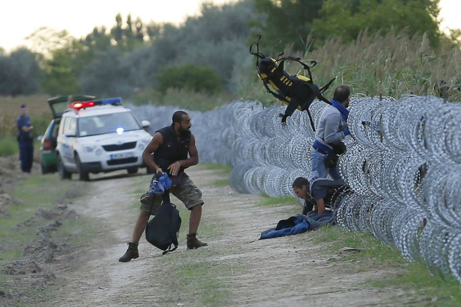 Hungarian police watch as Syrian migrants climb under a fence to enter the country