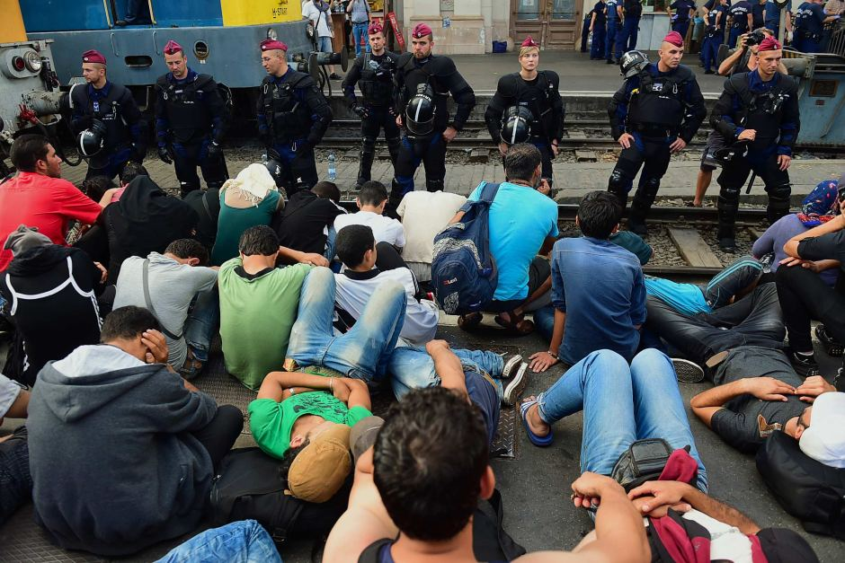 Riot police stand on the train track as they monitor asylum seekers.
