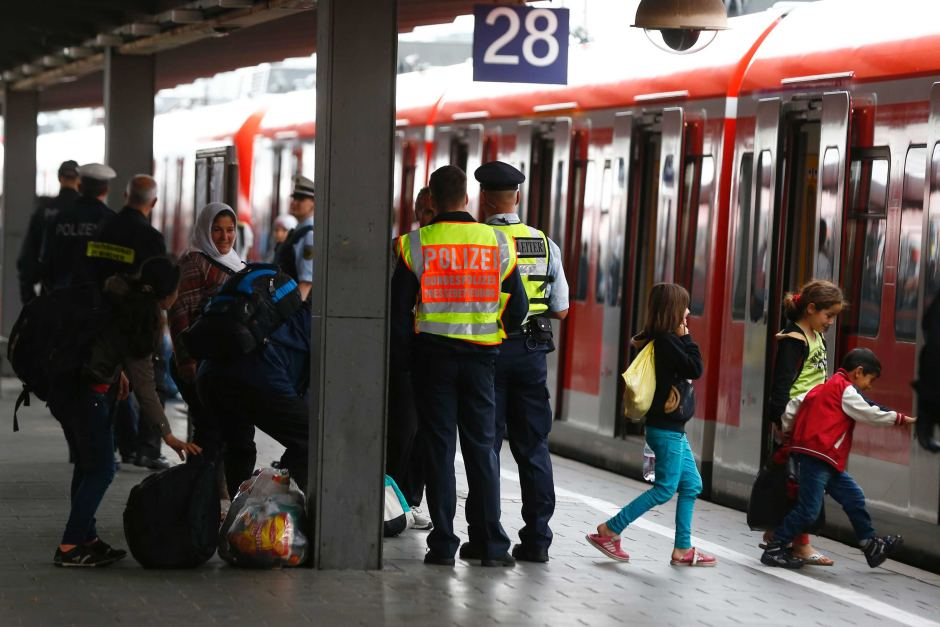 Police officers help migrants arriving with the first 'special' train from Salzberg